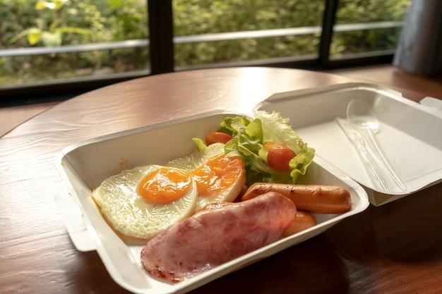 Amerikaanse ontbijtmaaltijd in een kartonnen doosje. kleine maaltijd van hammen en gebakken eieren.