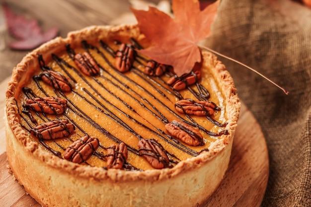 Amerikaanse pompoentaart versierd met chocolade en pecannoten op een houten tafel