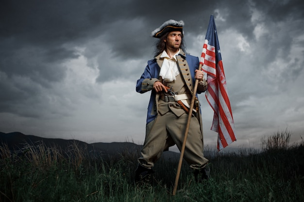 Amerikaanse revolutie oorlogsmilitair met vlag van kolonies over dramatisch landschap