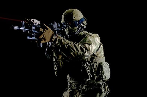 Amerikaanse soldaat in gevechtsmunitie met een wapen uitgerust met laservizieren richt zich op het doel. gemengde media