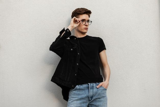 Amerikaanse stedelijke jongeman in modieus zwart spijkerjasje in stijlvolle jeans in vintage t-shirt zet buiten modebril op. knappe jongen in trendy kleding in de buurt van de muur in de stad. street style