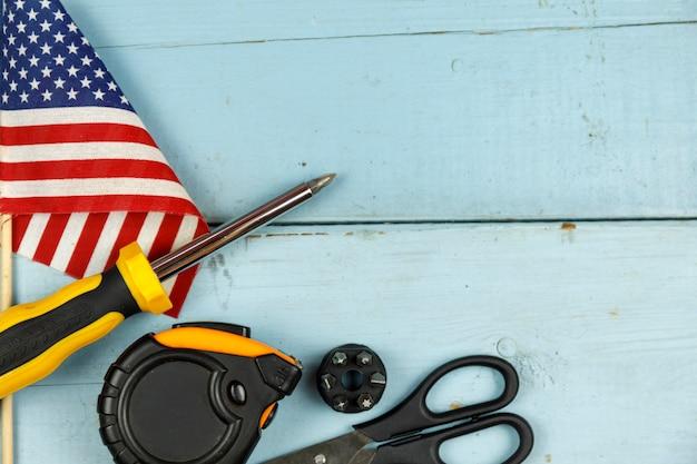 Amerikaanse vlag en bouwhulpmiddelen op blauwe houten achtergrond met exemplaarruimte