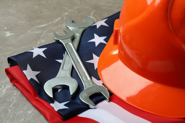 Amerikaanse vlag met bouwvakker en moersleutels op geweven grijs