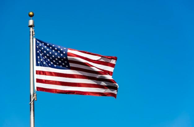 Amerikaanse vlag zwaaien tegen blauwe hemel, verenigde staten vlag zwaaien