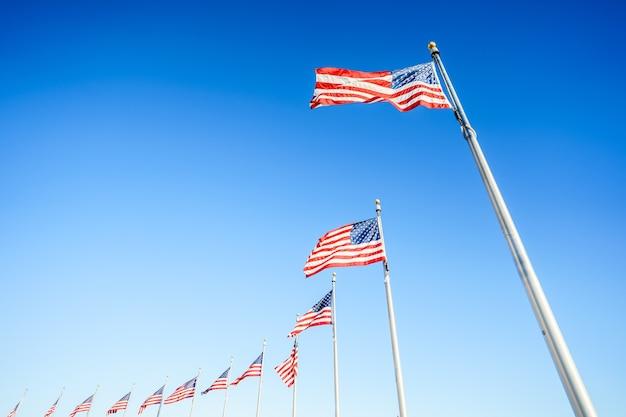Amerikaanse vlaggen op vlaggenmasten op blauwe lucht
