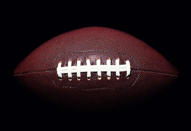 Amerikaanse voetbalbal die op zwart wordt geïsoleerd