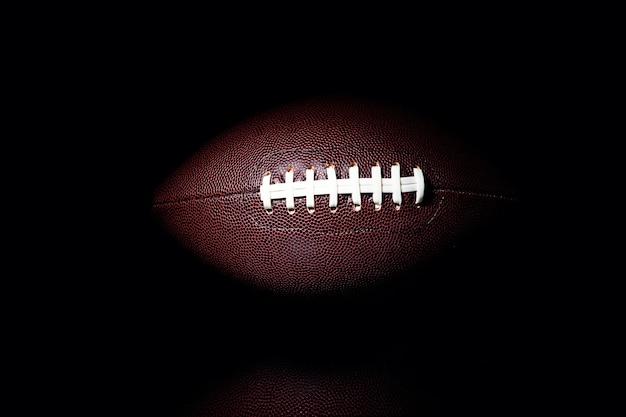 Amerikaanse voetbalbal die op zwarte ruimte wordt geïsoleerd