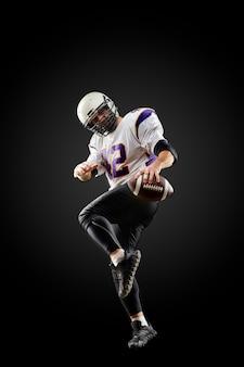 Amerikaanse voetballer in een sprong met een bal op een zwarte