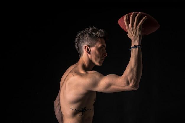 Amerikaanse voetballer met abs op zwart
