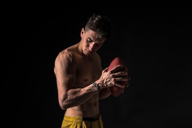 Amerikaanse voetballer naakt met abs op zwart