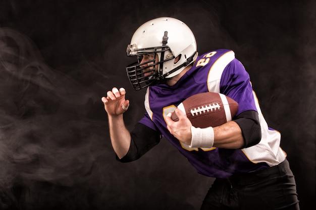 Amerikaanse voetbalster die de bal in zijn handen houdt. het concept van american football, motivatie, kopie ruimte