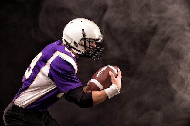 Amerikaanse voetbalster die de bal in zijn handen houdt. zwarte achtergrond, kopieer ruimte.