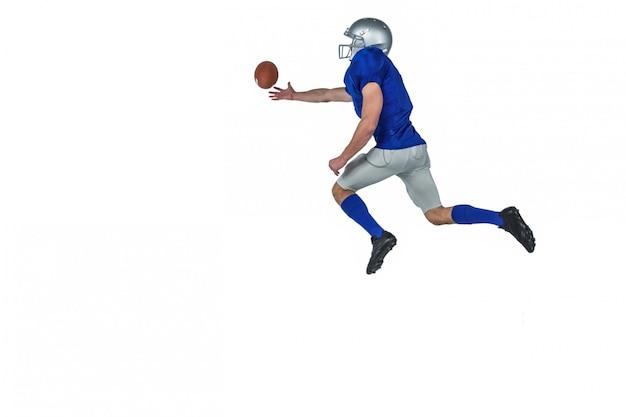 Amerikaanse voetbalster die de bal probeert te vangen