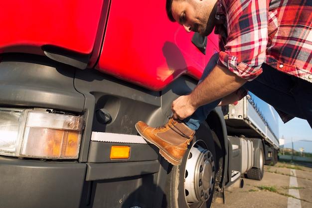 Amerikaanse vrachtwagenchauffeur die zijn laarzen vastbindt, klaar voor een lange rit.
