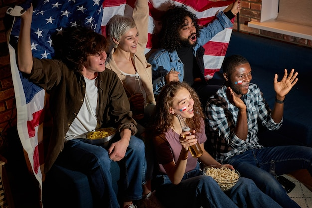 Amerikaanse vriendenfans kijken samen naar sportwedstrijden op tv, schreeuwen en schreeuwen van geluk, juichen thuis in de donkere kamer 's nachts