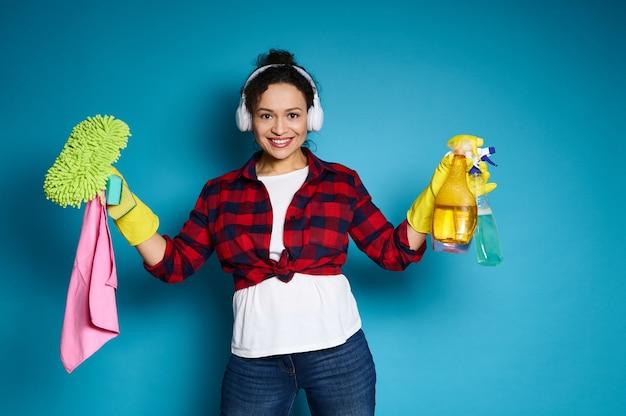 Amerikaanse vrouw die zich voordeed op camera met schoonmaakproducten, glimlachend met brede glimlach uiting van tevredenheid van behaald huiswerk