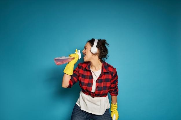 Amerikaanse vrouw, huisvrouw, met koptelefoon met reinigingssprays in haar handen en zingend met haar ogen dicht