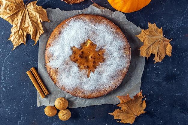Amerikaanse zelfgemaakte pompoen of appeltaart met walnoot en droge herfstbladeren op rustieke tafel.