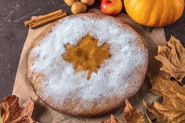 Amerikaanse zelfgemaakte pompoen of appeltaart met walnoot en droge herfstbladeren op rustieke tafel