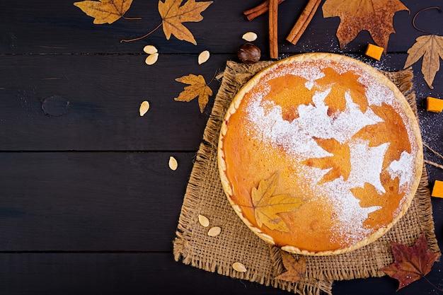 Amerikaanse zelfgemaakte pompoenpastei met kaneel en nootmuskaat, pompoenpitten en herfstbladeren op een houten tafel. thanksgiving eten. bovenaanzicht plat leggen