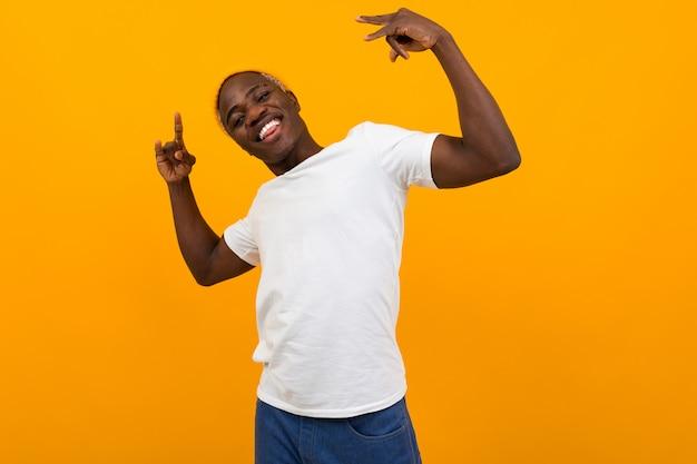 Amerikaanse zwarte man in een wit t-shirt op geel met handen omhoog