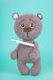 Amigurumi. diy speelgoed. gebreide bruine beerwelp met een thermometer. , preventie van kinderziekten