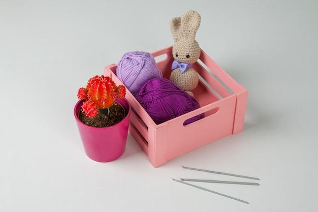 Amigurumi konijn met zwarte ogen en vlinderdas, cactus, wollen doos en haaknaalden