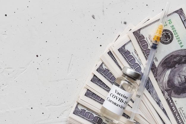 Ampul met vaccin en insulinespuit die op dollarbiljetten bepaalt