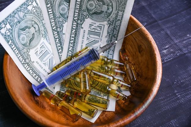 Ampullen met spuit en bankbiljetten in een houten kom
