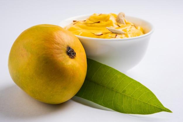 Amrakhand is een alphonso gearomatiseerde yoghurt of shrikhand, populair indiaas snoepje geserveerd met droog fruit en saffraan met hele mangofruit, op een kleurrijke achtergrond. selectieve focus