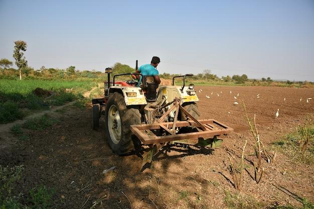 Amravati, maharashtra, india - 03 feb 2017: niet-geïdentificeerde boer in tractor die land voorbereidt voor het zaaien met zaaibedcultivator.
