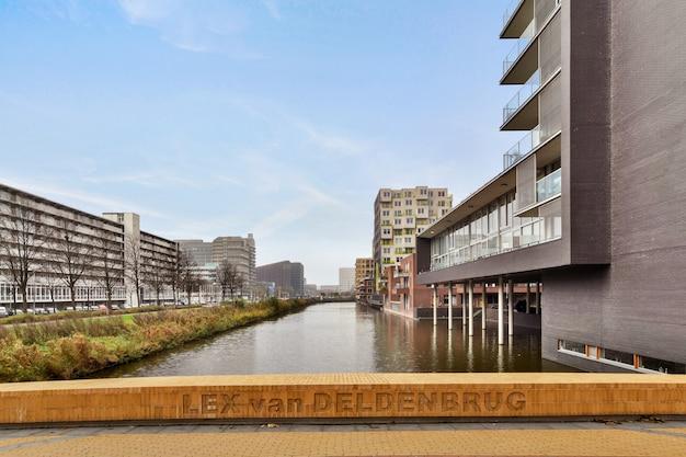 Amsterdam, nederland - 10 april, 2020: woonwijk met gebouwen met uitstekende gevel aan de rivier