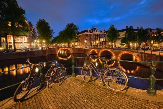 Amsterdamse gracht, brug en middeleeuwse huizen 's avonds