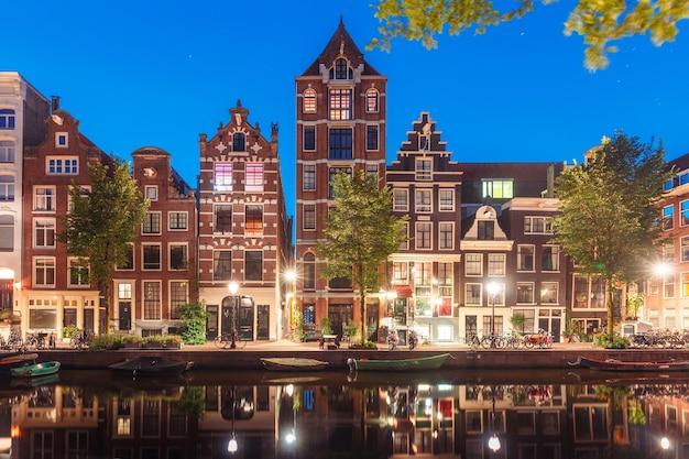 Amsterdamse gracht herengracht met typisch nederlandse huizen en hun reflecties tijdens ochtend blauwe uur, holland, nederland.