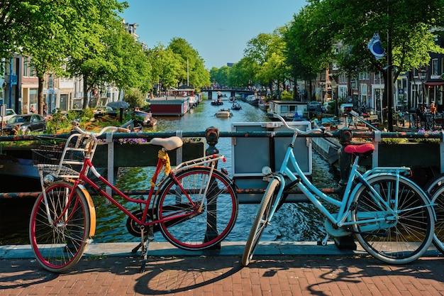 Amsterdamse gracht met boten en fietsen op een brug
