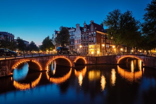 Amsterdamse grachtenbrug en middeleeuwse huizen in de avond