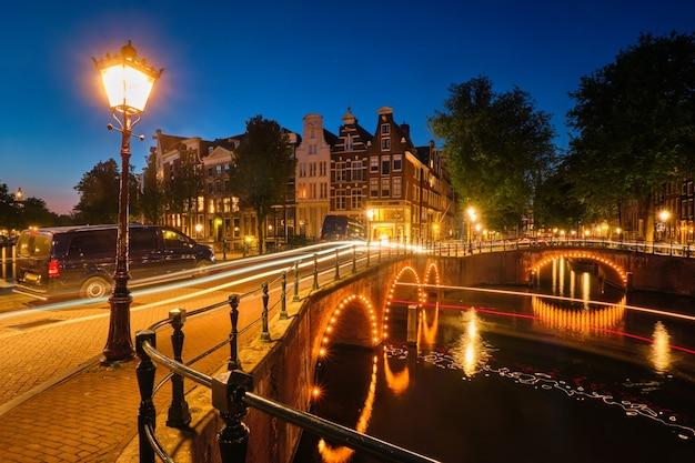 Amsterdamse kanaalbrug en middeleeuwse huizen in de avond