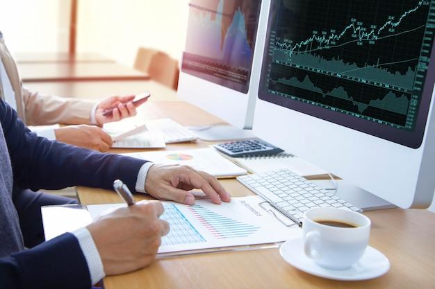 Analisten of zakenmensen voor moderne computerschermen die grafieken en financiële rapporten bekijken voor aandelenhandel of rendement op investering.