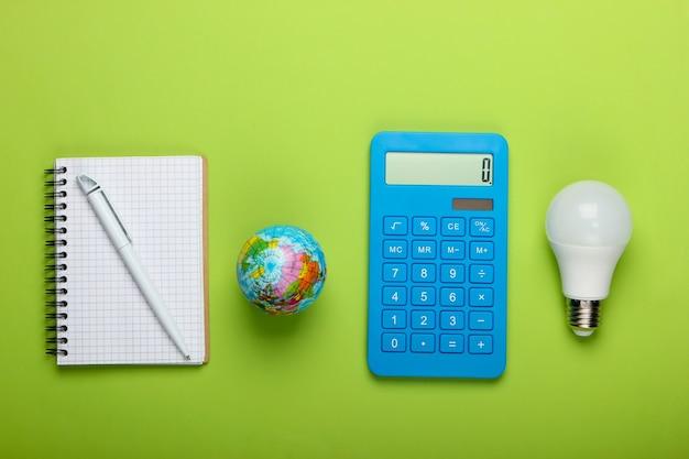 Analyse en statistieken van energieverbruik. eco concept. economie. rekenmachine en energiebesparende gloeilamp, globe, blocnote op groene achtergrond. bovenaanzicht