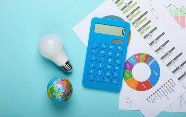 Analyse en statistieken van energieverbruik. eco concept. economie. rekenmachine met grafieken en diagrammen, energiebesparende gloeilamp, globe, kladblok op een blauwe achtergrond. bovenaanzicht