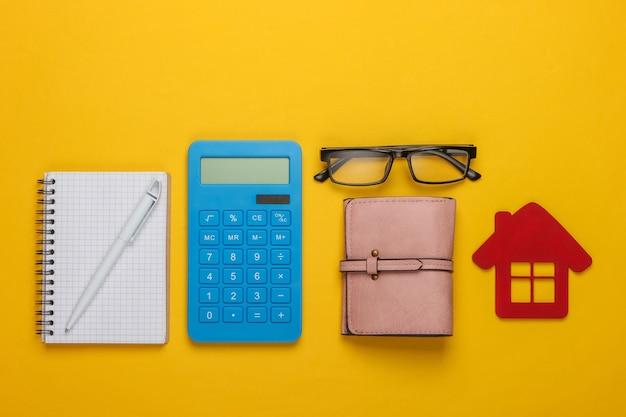 Analyse van de kosten van huisvesting of huur. berekening van het gezinsbudget. conceptueel schot op geel. plat leggen