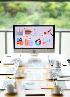 Analyse verkoopdoel groei grafiek grafiek investeringsrapport gegevens op grote computerschermmonitor geplaatst in het midden van de vergadertafel voor glazen ramen met uitzicht op de tuin op onscherpe achtergrond.