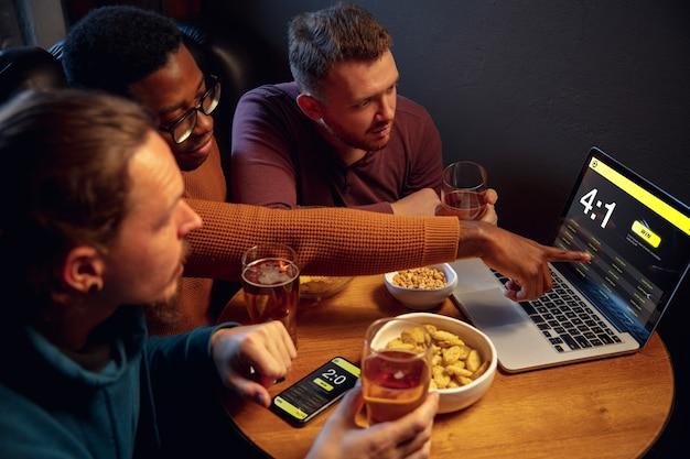 Analyseren. opgewonden fans in bar met bier en mobiele app om te wedden, scoren op hun apparaten. scherm met wedstrijdresultaten, emotionele vrienden juichen. gokken, sport, financiën, modern techn-concept.