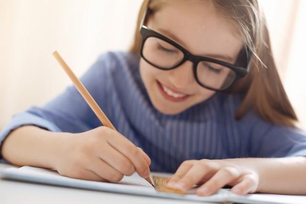 Analytisch, vrolijk, charmant meisje dat speciaal gereedschap gebruikt om een mooi schema te maken terwijl ze haar huistaak voltooit