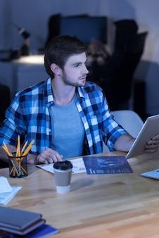 Analytisch werk. hardwerkende ijverige aardige man die naar de afbeeldingen kijkt en de gegevens vergelijkt terwijl hij op kantoor werkt