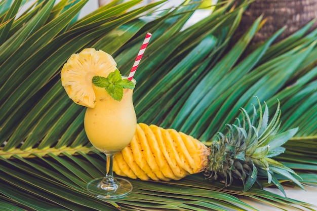 Ananas en ananassmoothies tegen een tak van een palmboom.