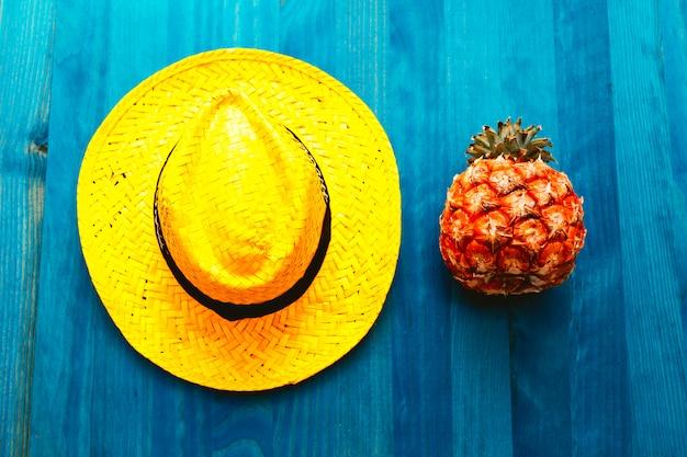 Ananas en strohoed. cocktail aan het strand. tropische minimaal. frisse ideeën