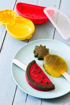 Ananas en watermeloen ijslollys op blauwe houten tafel