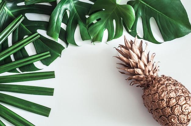 Ananas gouden kleur met tropische bladeren op witte achtergrond, zomer concept