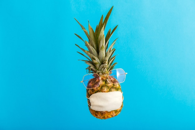 Ananas grappig gezicht in stijlvol zonnebril medisch masker op een blauwe zomerachtergrond in kleur. reisconcept ananas in beschermend masker in coronavirusvergrendeling.